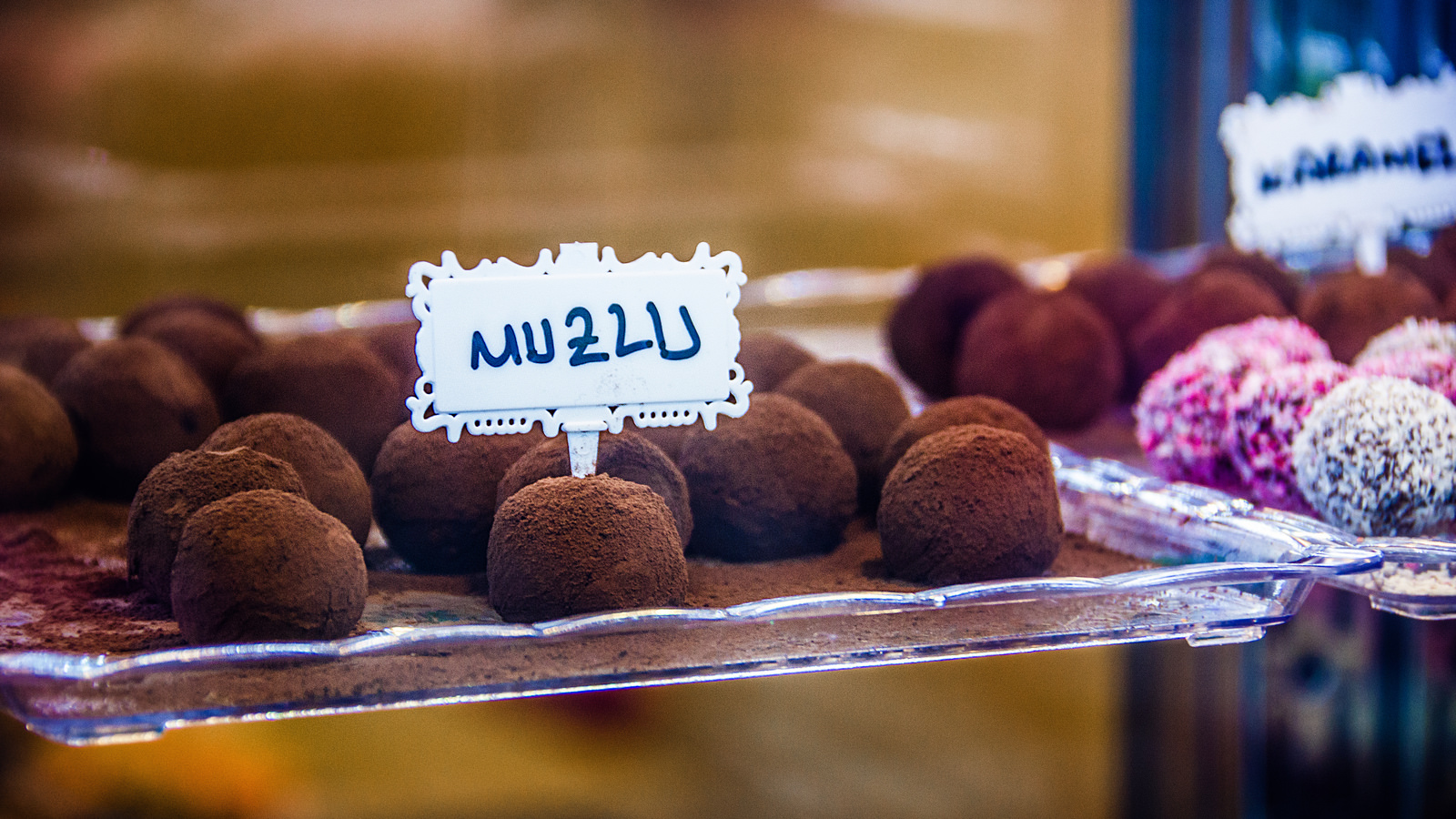 A photo of some chocolate truffles in a window display.