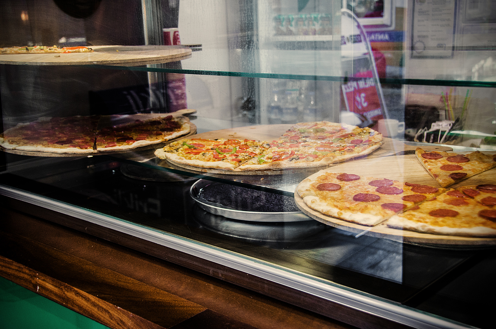A photo of pizzas on platters in a display window.