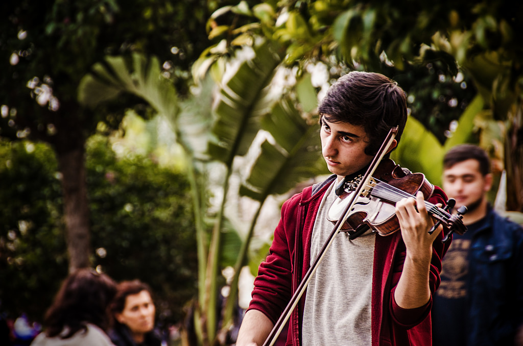 A photo of a violinist playing on the street near Old Owl Café in Antalya.